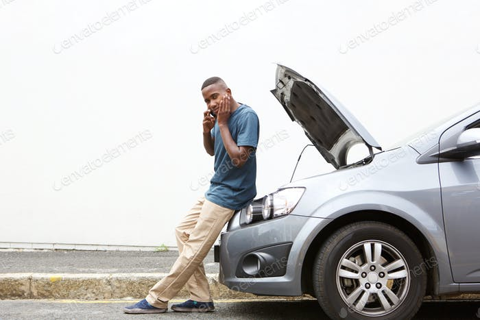 Stressed young man calling for help on phone for his broken car