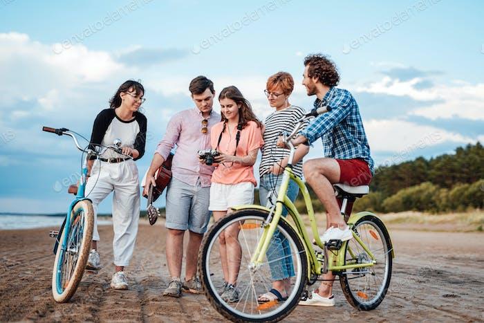 Fünf glückliche Freunde mit ihren Fahrrädern am Strand