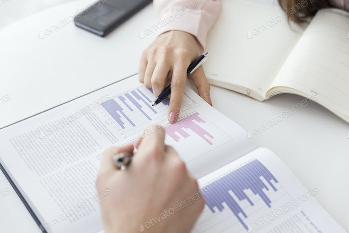 Cropped image of hands analyzing graphs in meeting