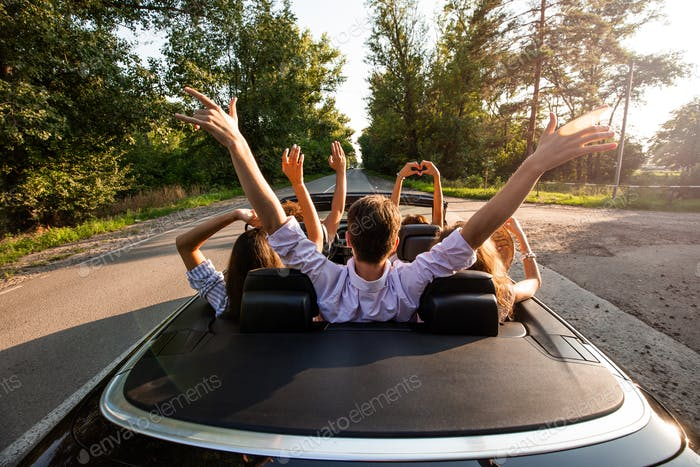 ompany of young people riding in a cabriolet on the road and holding their hands up on a warm sunny