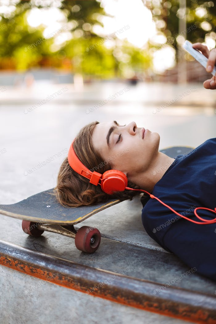 Close up thoughtful guy in orange headphones lying on skateboard