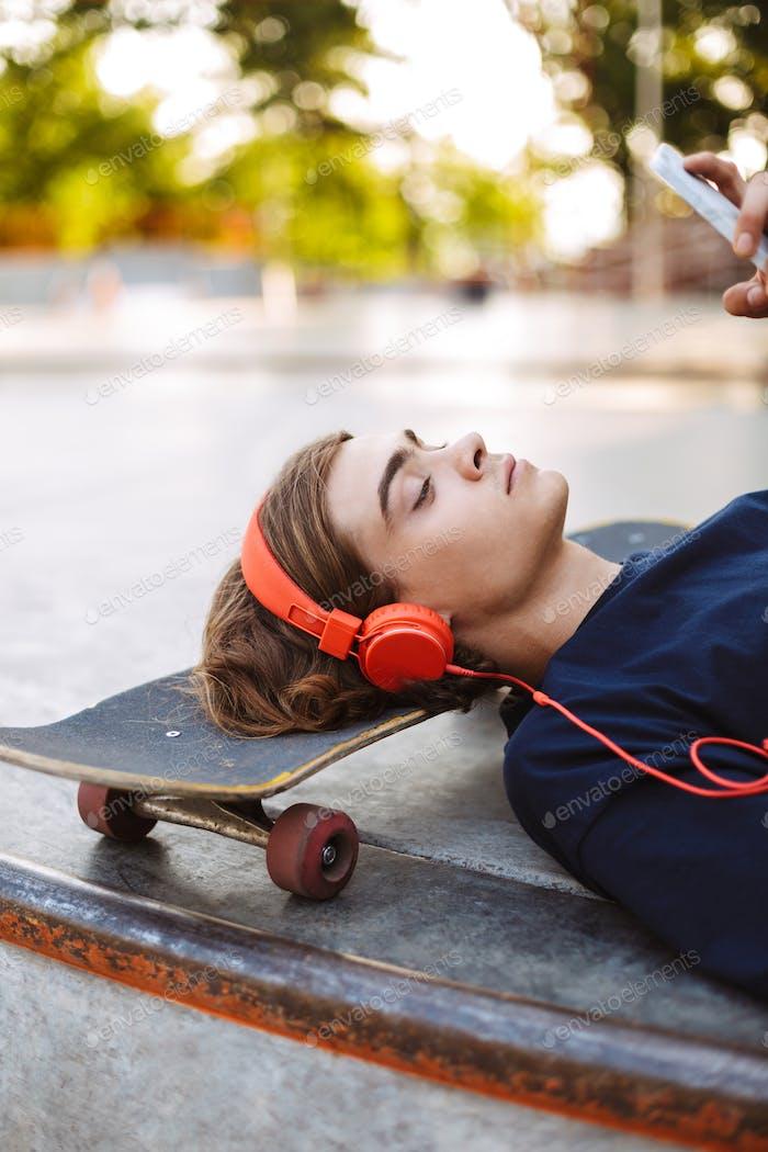 Cerca de arriba reflexivo chico en naranja auriculares acostado en monopatín