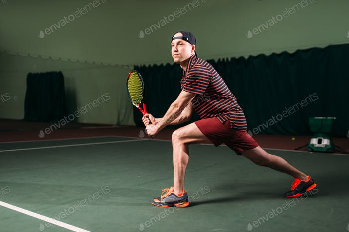 Man with tennis racket playing on indoor court