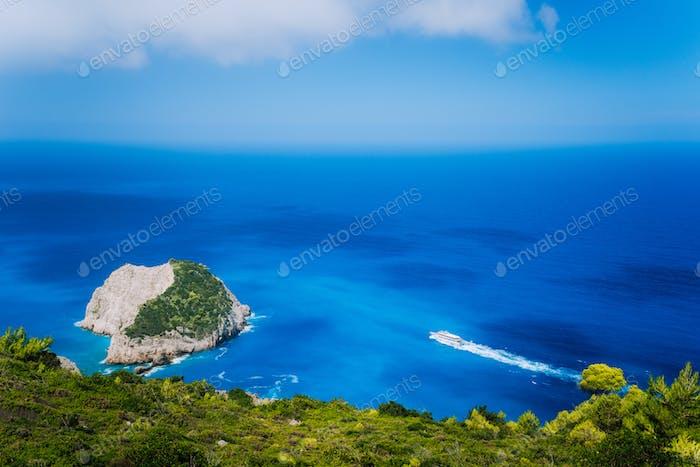 Zakynthos fantastic west coastal view with white cliff. White tourist ship sailing full speed on