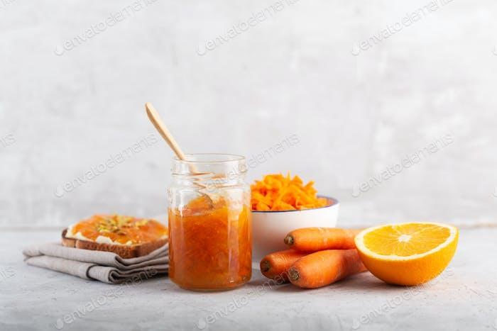 Karottenmarmelade mit Orangensaft auf einem grauen Hintergrund