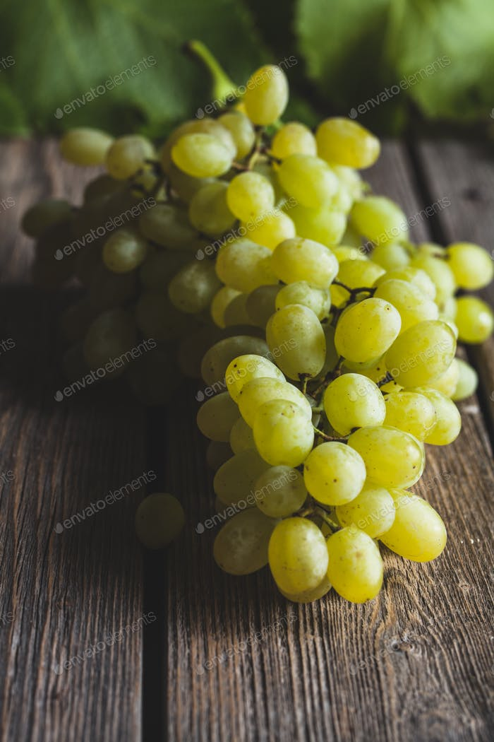 fresh Green grape with leaves on wooden background. Wholesome healthy food