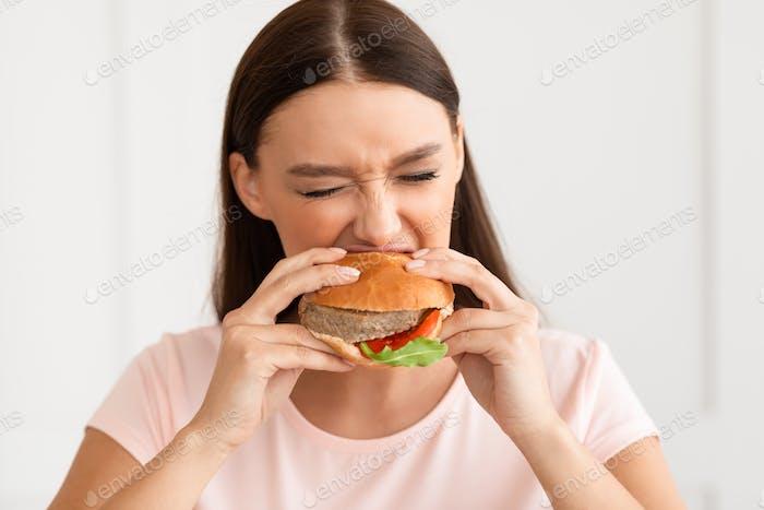 Fille manger Burger profitant de la restauration rapide à la maison