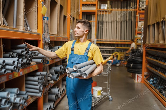 Male builder choosing piping in hardware store