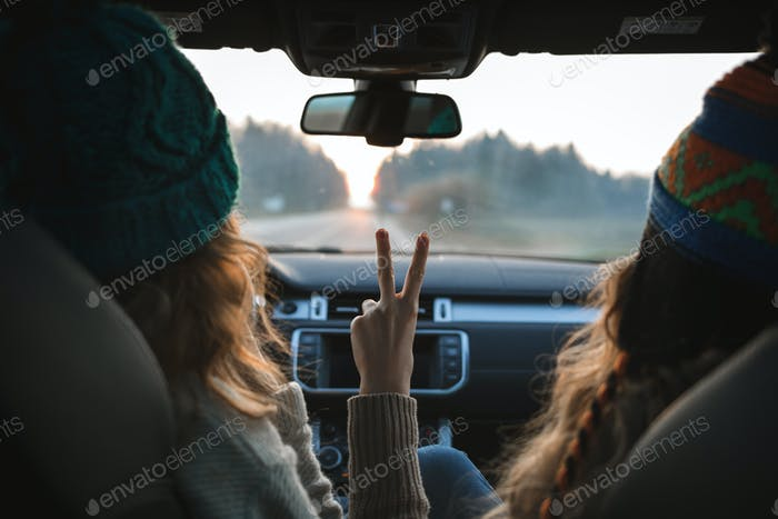 two girls sitting in the car, looking forward, showing peace sign