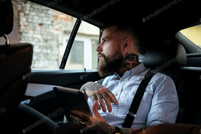 Portrait of bearded man with tattoes in the car