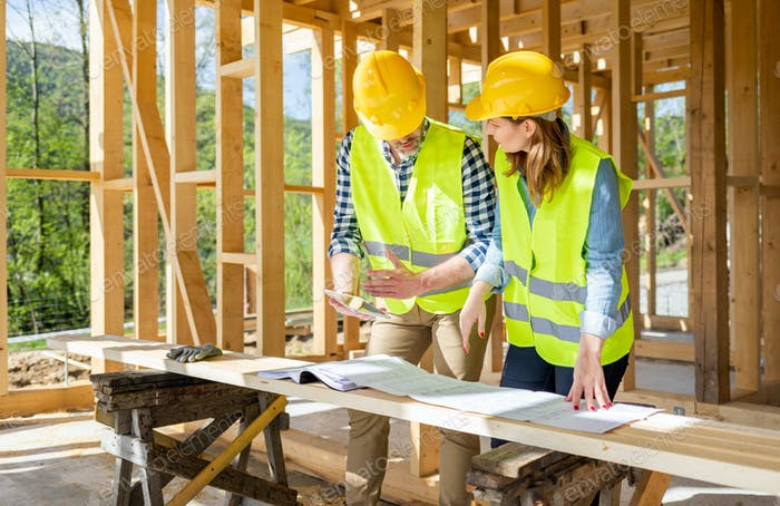 Ingenieure arbeiten auf der Baustelle halten Blaupausen von Holzrahmenhaus