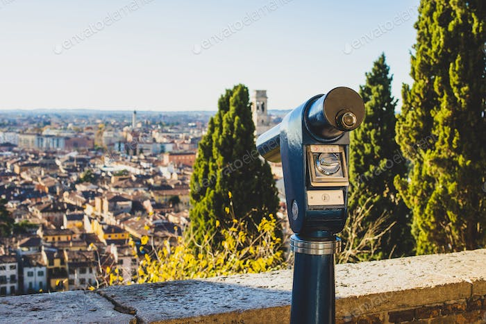 A close up photo of a public monocular on the top of a mountain