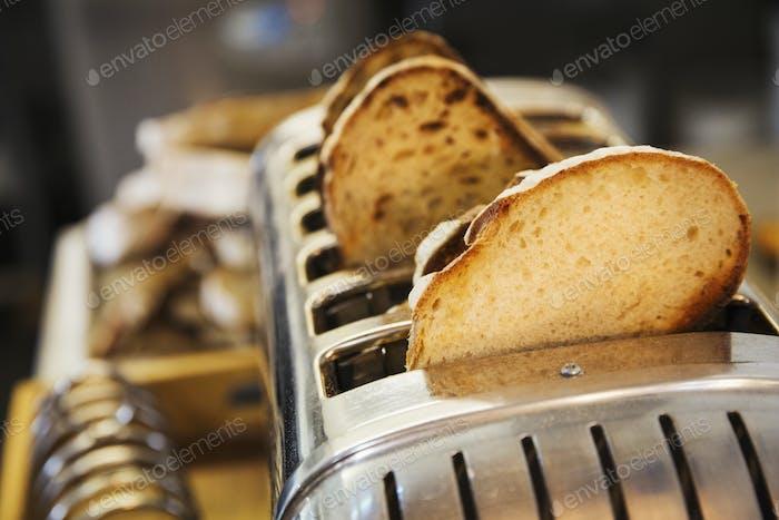 Nahaufnahme von Brotscheiben in einem Edelstahl-Toaster.