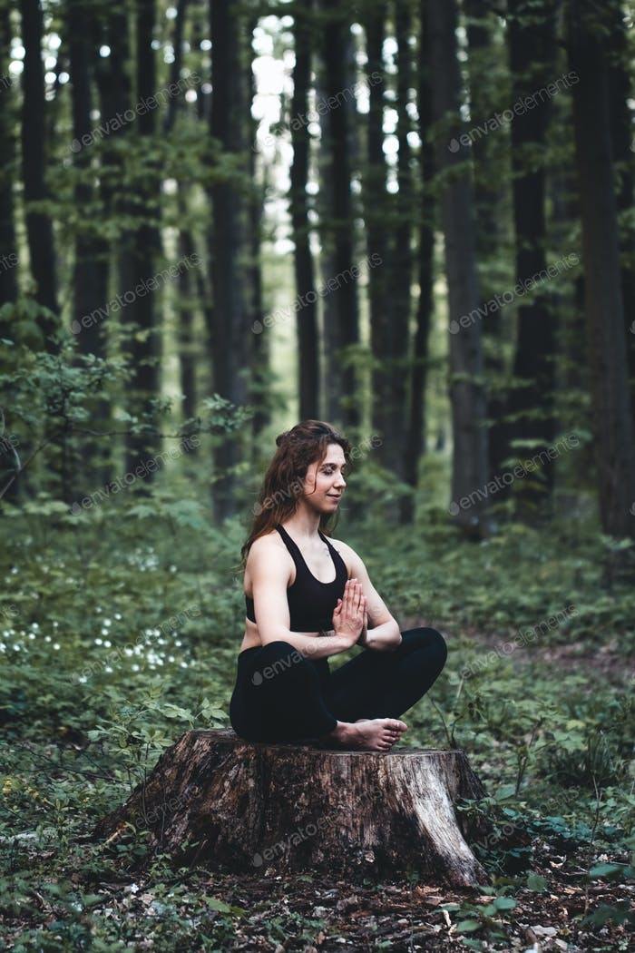 Young girl practices yoga in the forest, the concept of enjoying privacy and concentration, sunlight