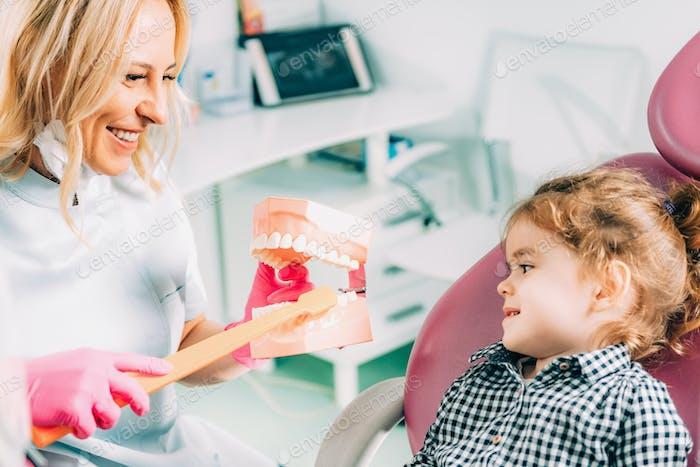Kleines Mädchen in der Zahnklinik, lernen, wie man Zähne correc putzen