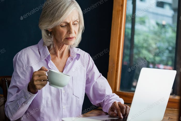 Senior woman drinking coffee while working on laptop at table
