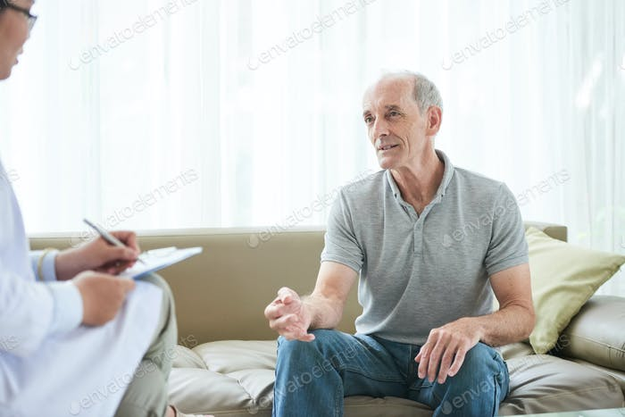 Senior man sharing problems with doctor