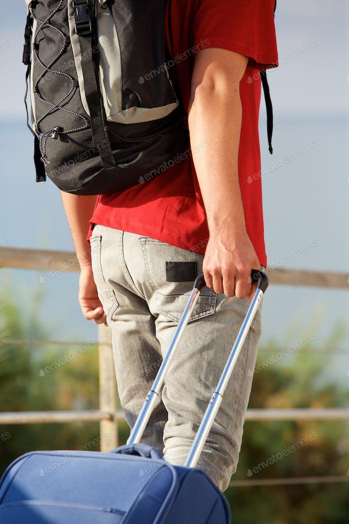 Mann zu Fuß mit Rucksack und ziehen Koffer