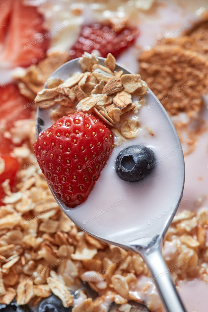 Close-up of spoon with fresh natural homemade morning breakfast with strawberries, milk dessert, oat