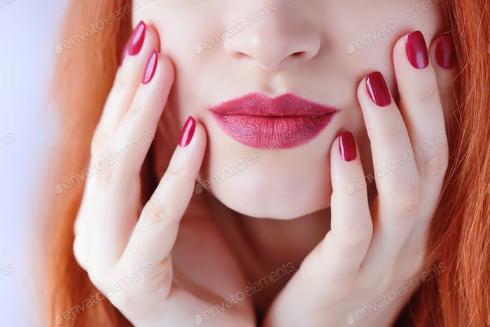 Beautiful red-haired young woman with red manicure, lipstick sam