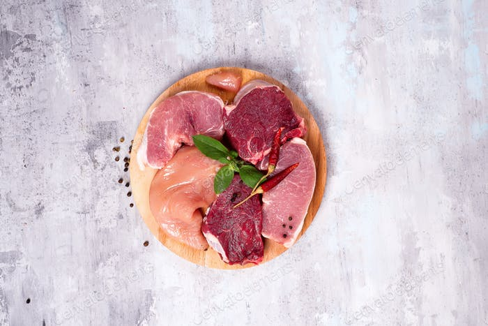 Different types of meat on a wooden board. Lean proteins.