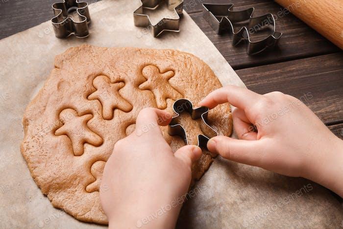Kinderhände machen festliche Weihnachten Lebkuchenplätzchen