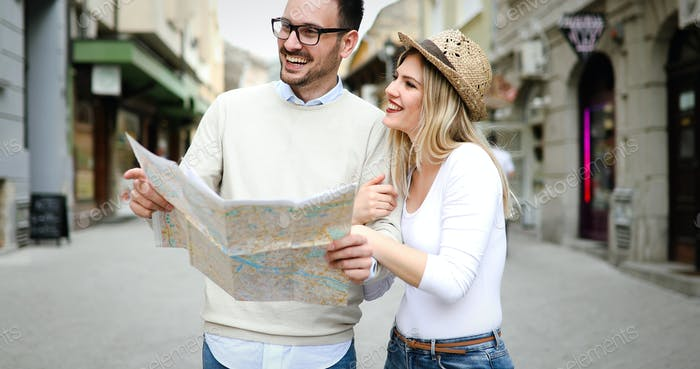 Smiling couple in love traveling with a map outdoors