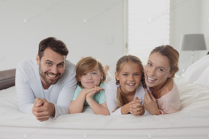 Portrait of happy Caucasian family lying on bed and looking at camera in bedroom at home