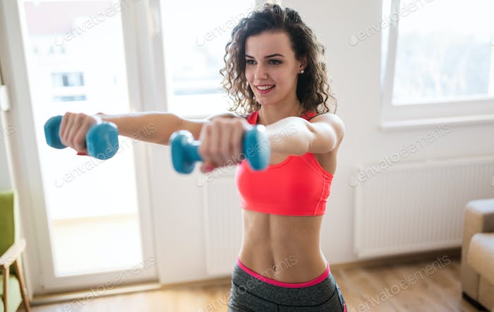 Sporty woman exercising at home to stay fit