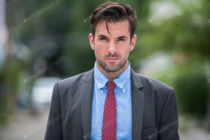 Young handsome Hispanic businessman wearing suit outdoors