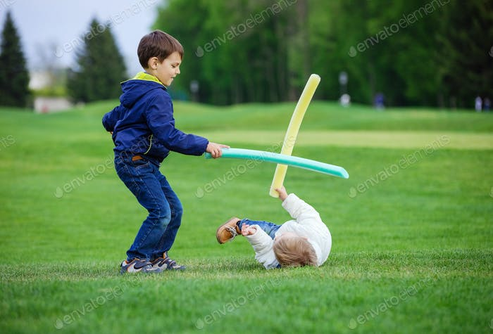 Preschool boys fighting with toy swords