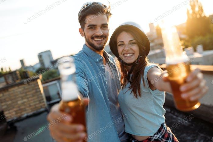 Happy couple enjoying drinks and balcony