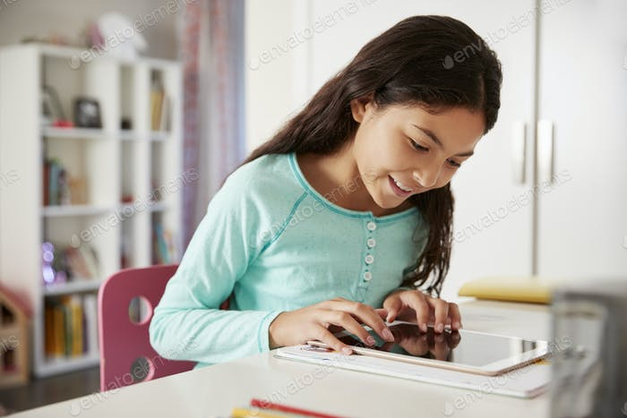 Young Girl Sitting At Desk In Bedroom Using Digital Tablet To Do Homework