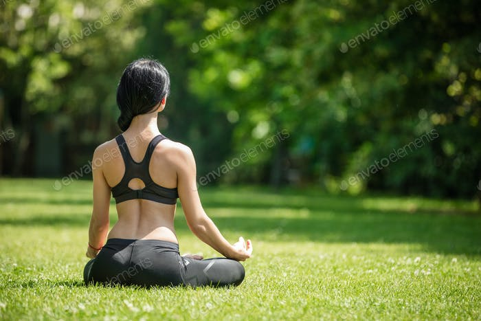 Young girl practicing yoga outdoors