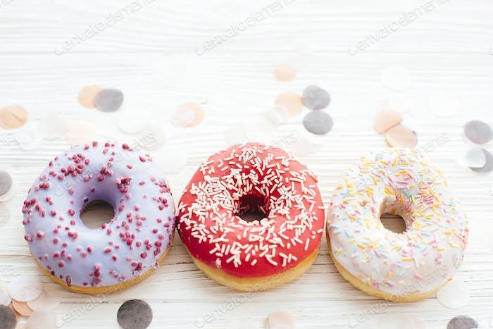 Donuts mit Streuseln und Marshmallows auf weißem Tisch mit Konfetti