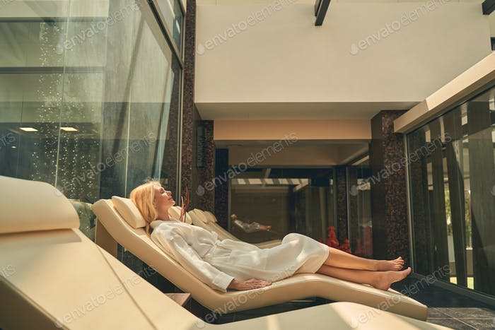 Serene woman is relaxing after spa procedure in rest room