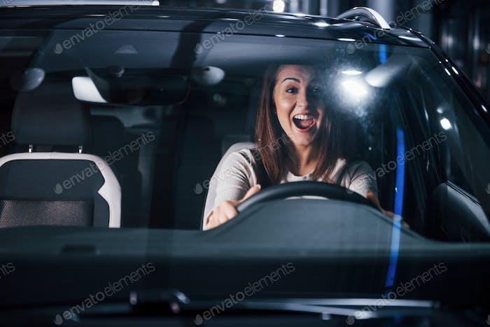 Junge Frau ist in einem brandneuen, modernen Automobil
