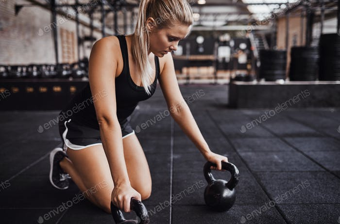 Young woman prepraring to exercise with weights in a gym