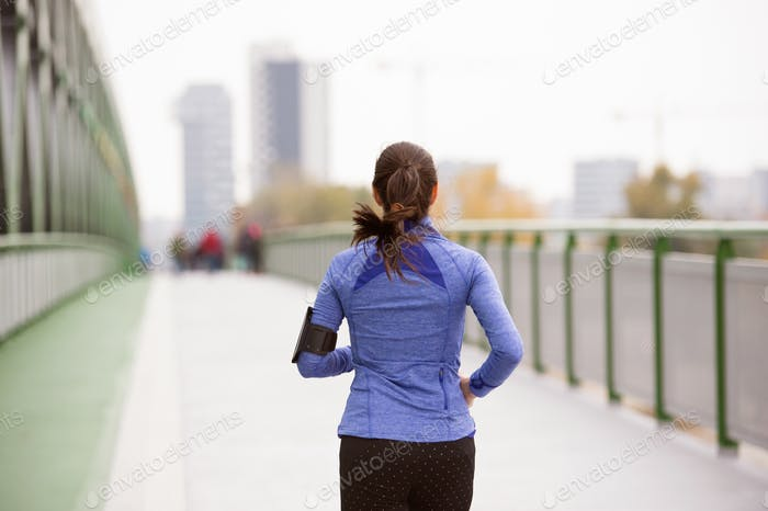 Young woman in the city running on green steel bridge