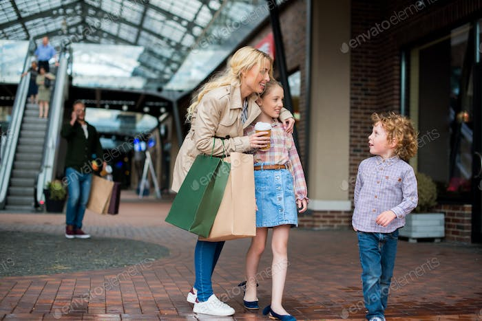 young mother talking with her little kids during shopping at shopping centre