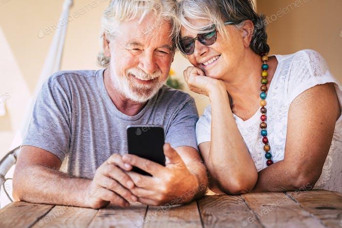 Happy beautiful senior old couple do a phone call