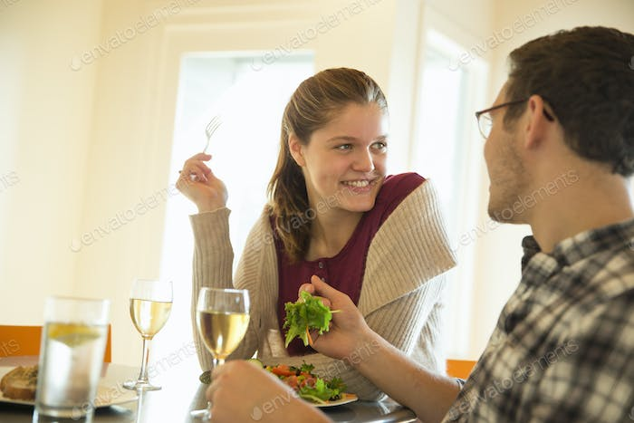 A young man and woman sitting together having a meal and drinking wine.