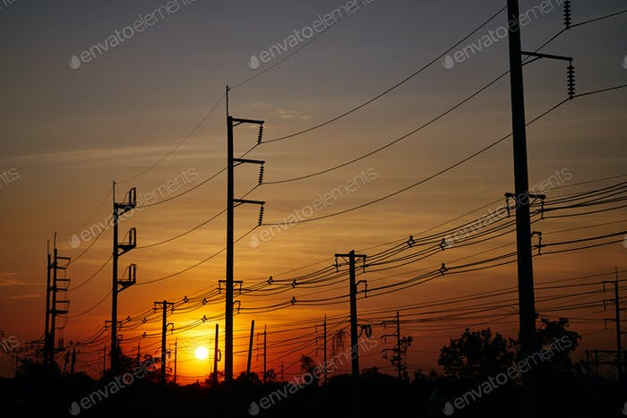 Die elektrischen Pole und elektrischen Leitungen mit einem Himmel des Sonnenuntergangs
