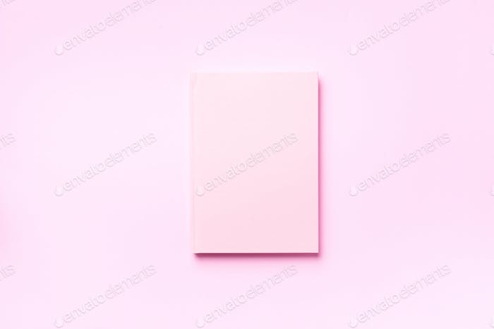 Top view of open pink notebook on pastel colorful background. Copy space. Woman business, study