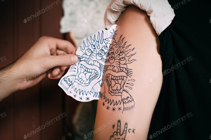 обрезанный снимок татуировщика, передающего эскиз татуировки на плече в тату-салоне