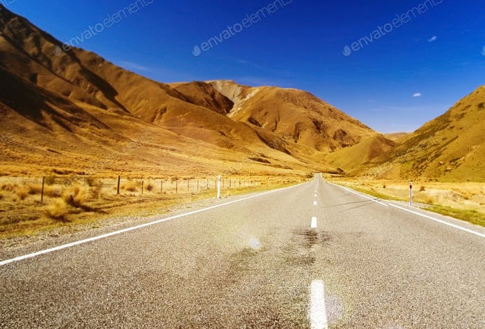 Continuous Road in a Scenic with Mountain Ranges Afar Concept