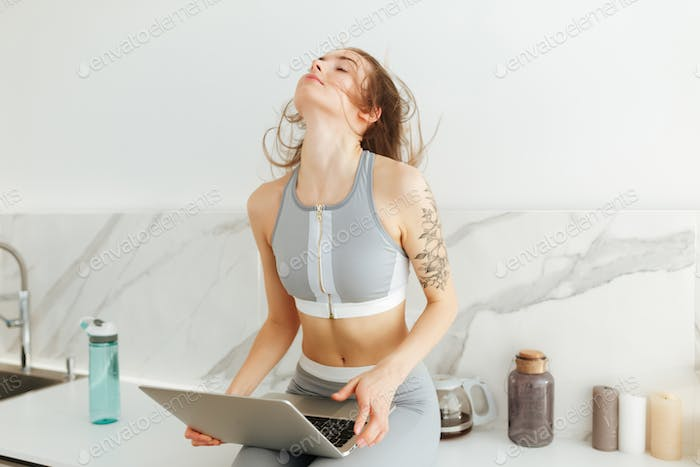Pretty girl in sporty top and leggings sitting on kitchen table with laptop in hand