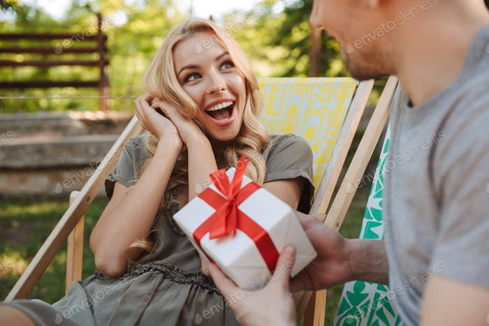 Cropped view of man giving a gift box to woman