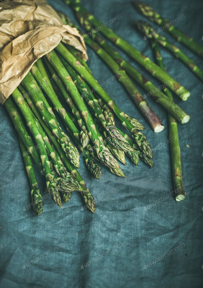 Fresh green asparagus in craft paper bag, copy space
