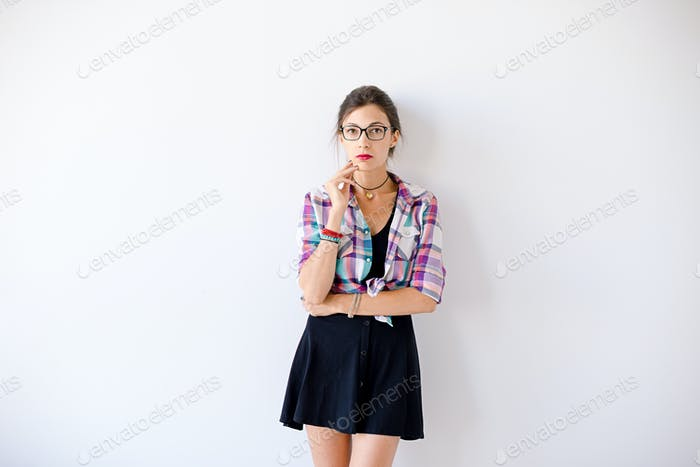 Young woman wearing fashionable glasses and plaid colorful shirt
